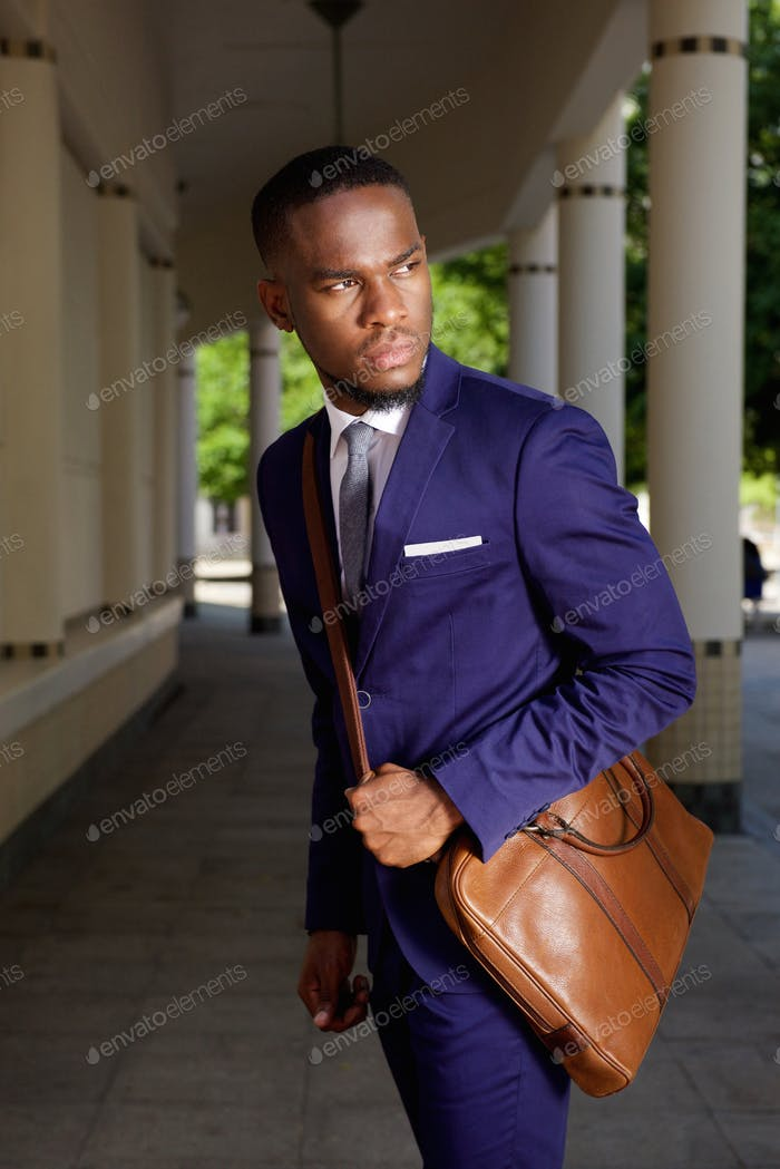 Young businessman standing with leather shoulder bag