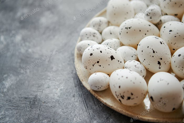 Composition of white traditional dotted Easter eggs in white ceramic plate