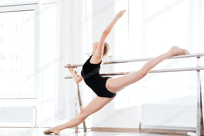 Frau Ballerina Stretching in der Nähe Stock an Wand im Tanzstudio
