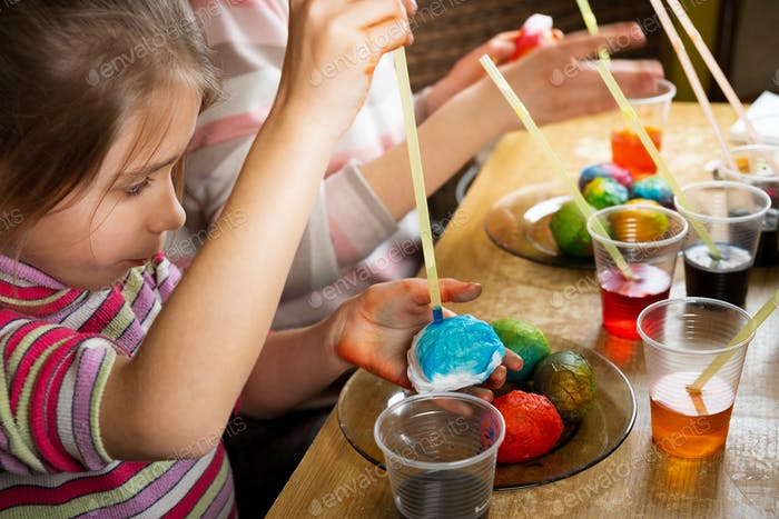 Children paint Easter eggs with colorful dyes in an unusual way