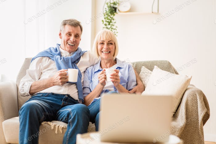 Mature couple watching film on laptop and drinking coffee