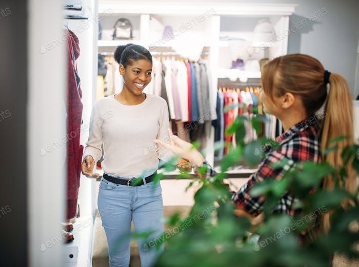 Two female friends choosing coat in shop, shopping