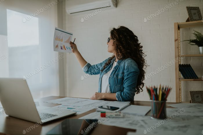 Photo of business woman analyzing printed reports and charts while sitting at office desk.
