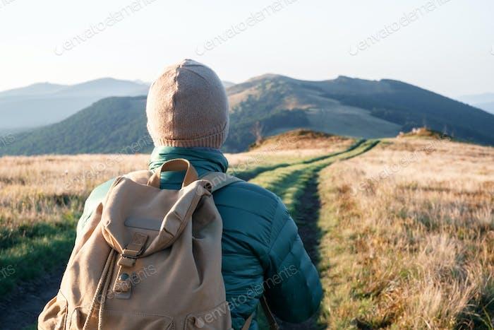Mann mit Rucksack auf Bergstraße