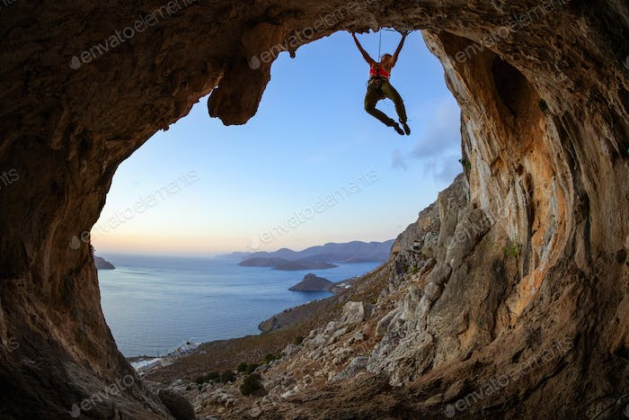 Young woman climbing on ceiling in cave at sunset