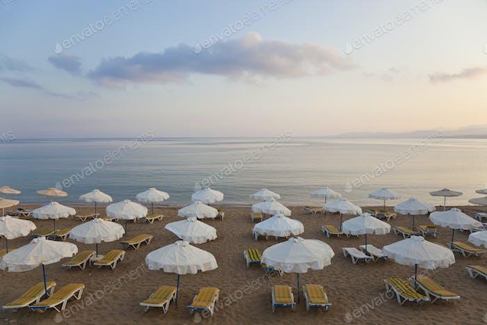 Hochwinkelansicht der Reihen von Liegestühlen und Sonnenschirmen an einem Sandstrand im Mittelmeer.