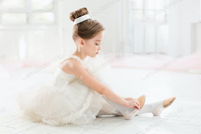 Die kleine Balerina in weißem Tutu im Unterricht an der Ballettschule