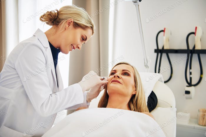 Doctor doing botox injections on a mature woman's face