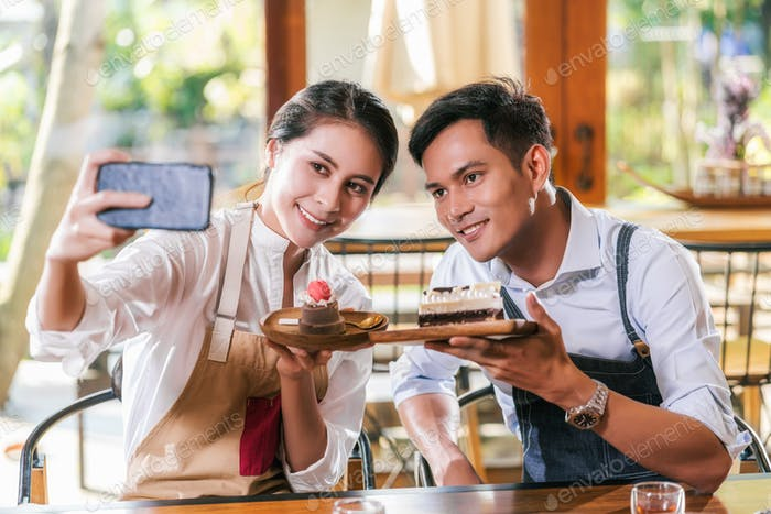 Couple Asian two partner of small business owner taking selfie and presenting the bakery
