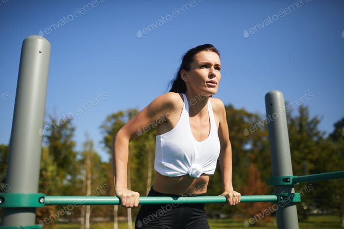 Athletic lady breathing deeply while doing dips on bar