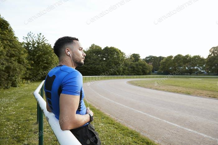 Male athlete wearing earphones taking a break at a track