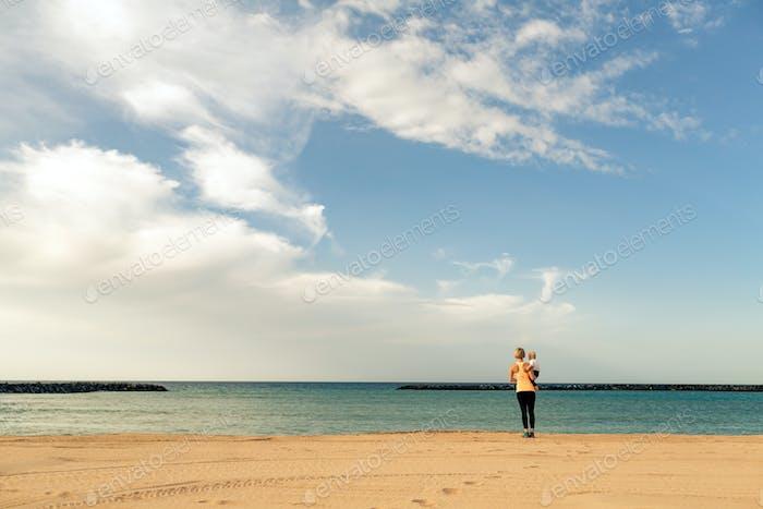 Madre con Bebé niño disfrutando Amanecer en una Playa