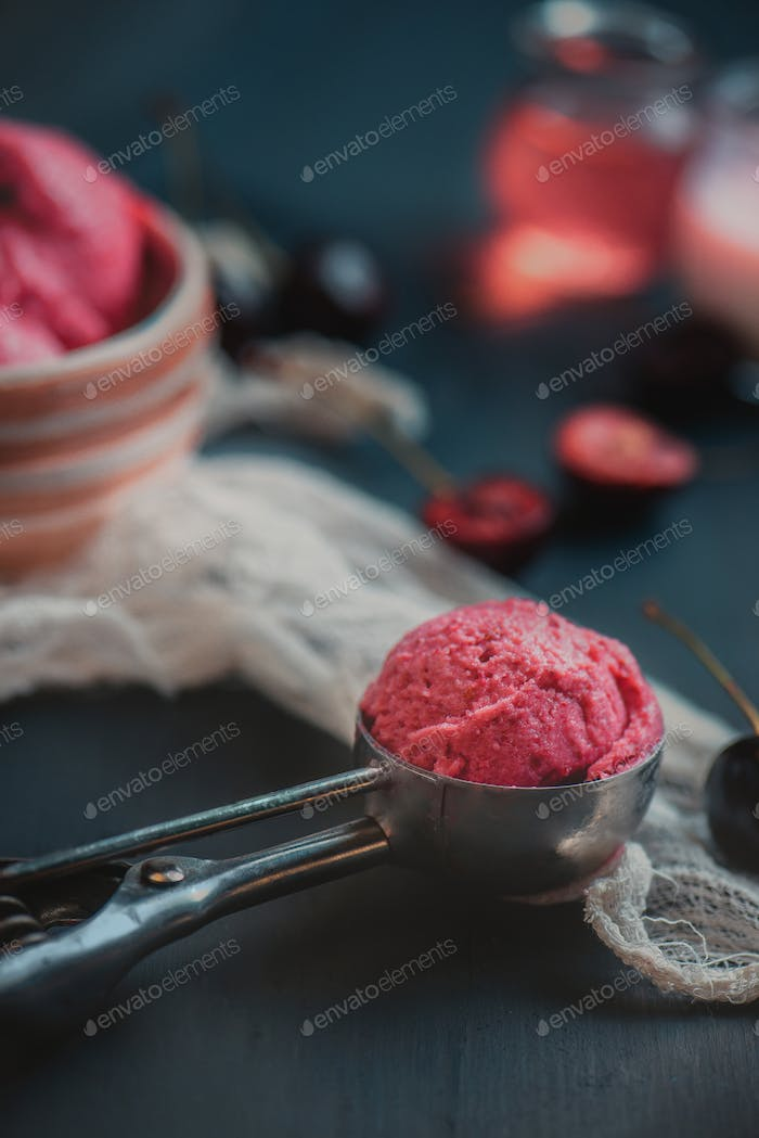 Homemade pink ice cream in ice cream spoon with cherries and plums. Dark food photography with copy