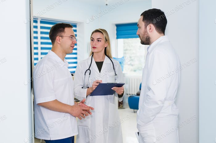high angle view of three doctors in white coats having conversation at hospital hall