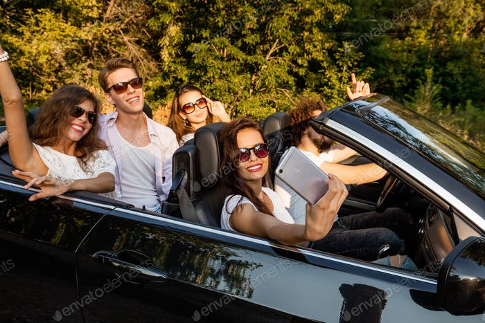 Group of young girls and guys are making selfie in a black cabriolet on a warm sunny day