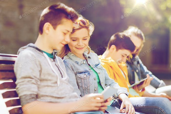 happy teenage friends with tablet pc outdoors
