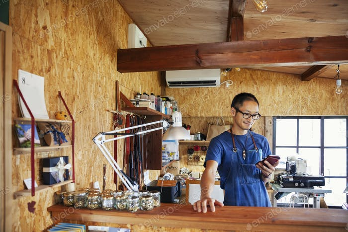 Japanese man wearing blue apron and glasses standing in a leather shop, using his mobile phone.