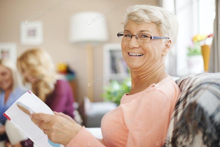 Retrato de sonriente mujer mayor leyendo periódico