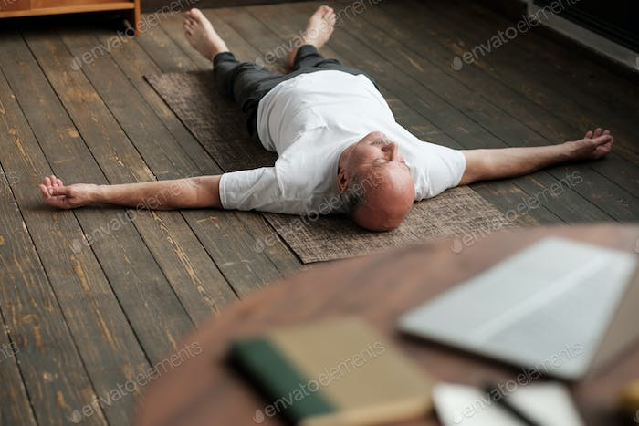 Man meditating on a wooden floor and lying in Shavasana pose after practice
