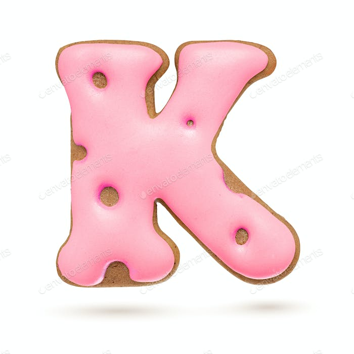 Capital letter K. Pink gingerbread biscuit isolated on white.