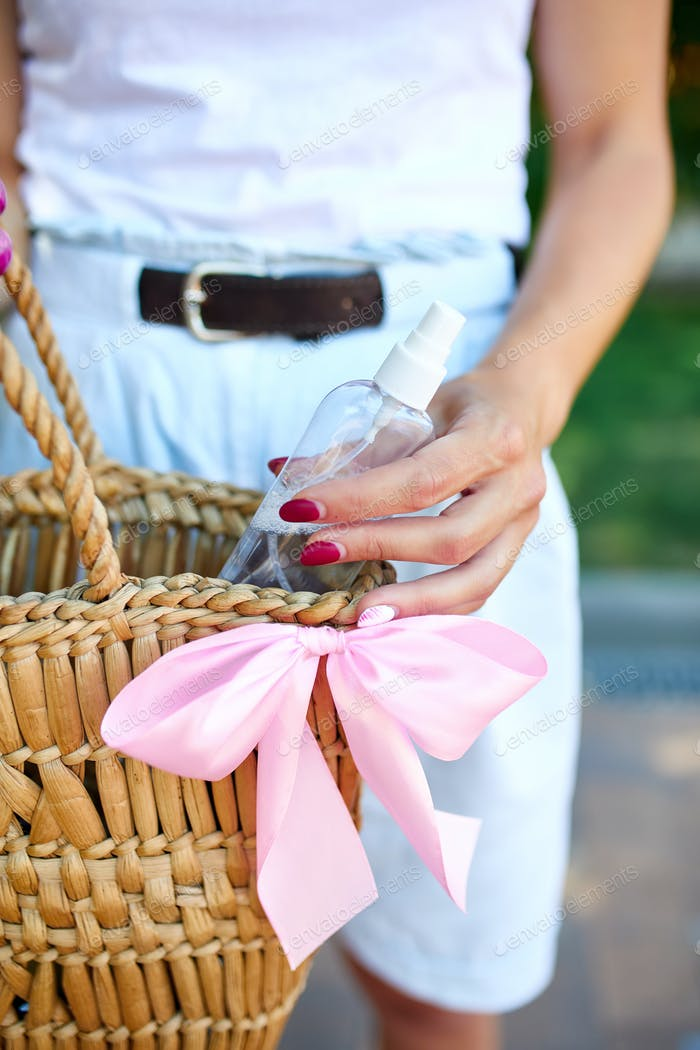 Hand of trendy woman in with straw bag with disinfecting hands gel in handbag.