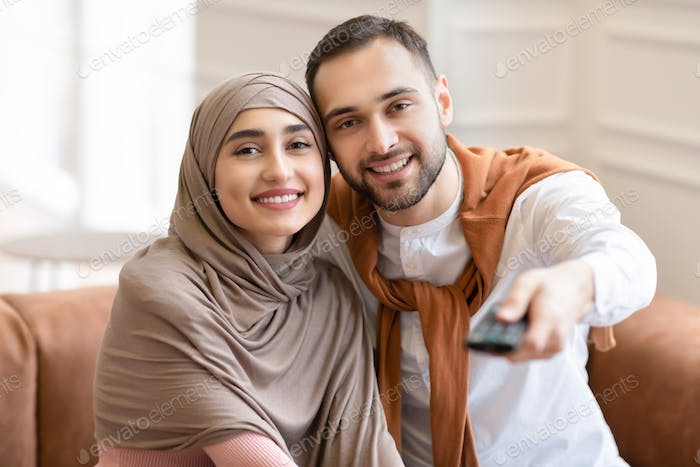 Young Muslim Spouses Watching Television Sitting On Couch At Home