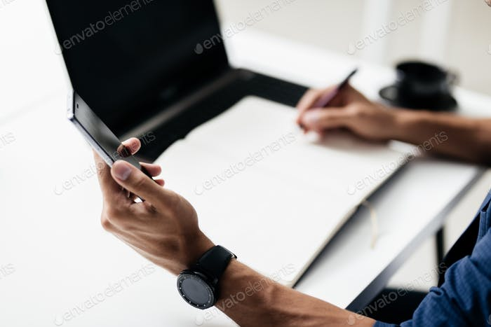 Man makes notes in a notebook on a table and keeps a phone in his hand