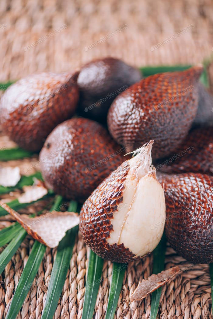 Red Salacca. Salak, snake fruits with palm leaves on rattan background. Copy space. Salacca zalacca