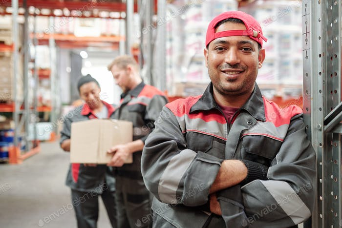 Happy young Latino man in workwear and gloves crossing arms by chest