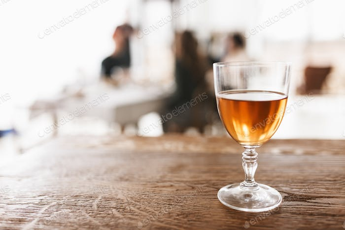 Close up glass of wine on wood table in cozy kitchen with fuzzy background