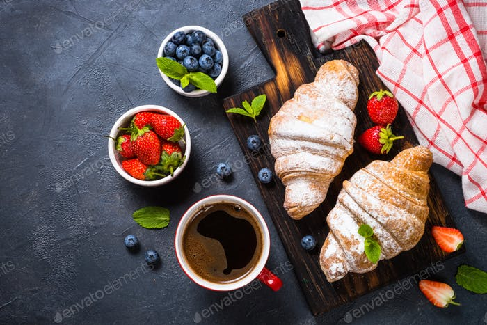Croissant with fresh berries and cup of coffee on black