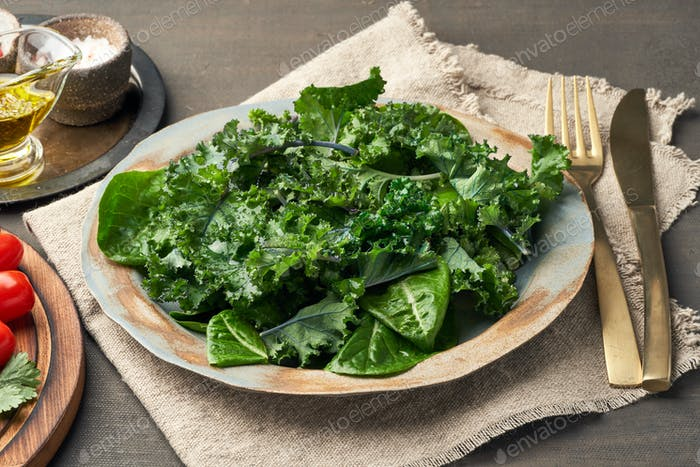 Salad kale, leaf cabbage, cos lettuce green mixture in plate. Undressed fresh leaves. Vegan