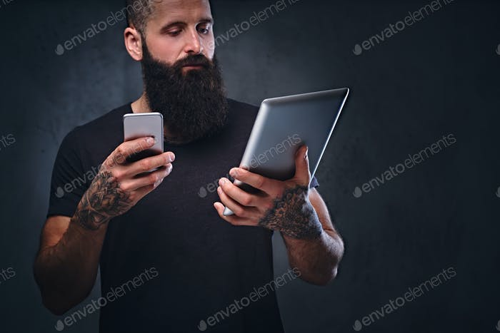 A man holds tablet PC and smartphone.