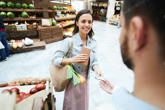 Happy woman paying for organic food