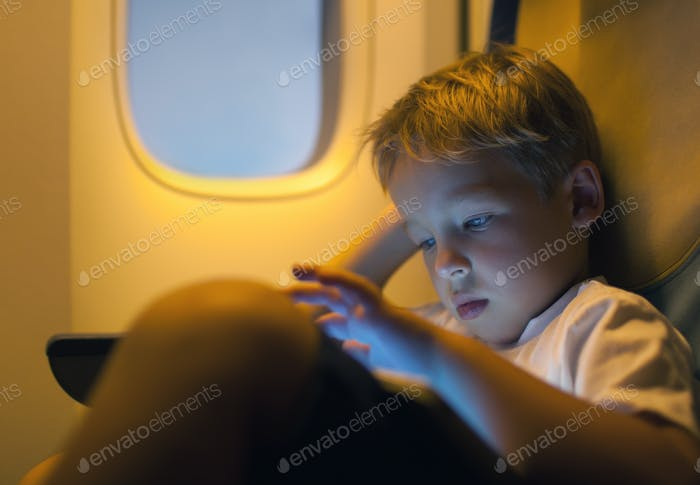 Little boy using tablet computer during flight