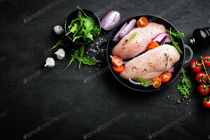 Fresh raw chicken meat, fillet marinated with spices, onion and tomatoes. Top view