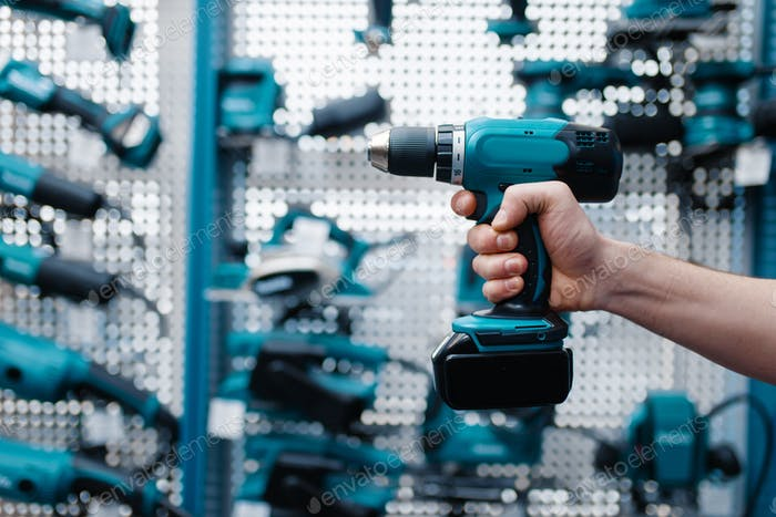 Male worker hand holds electric drill, tool store