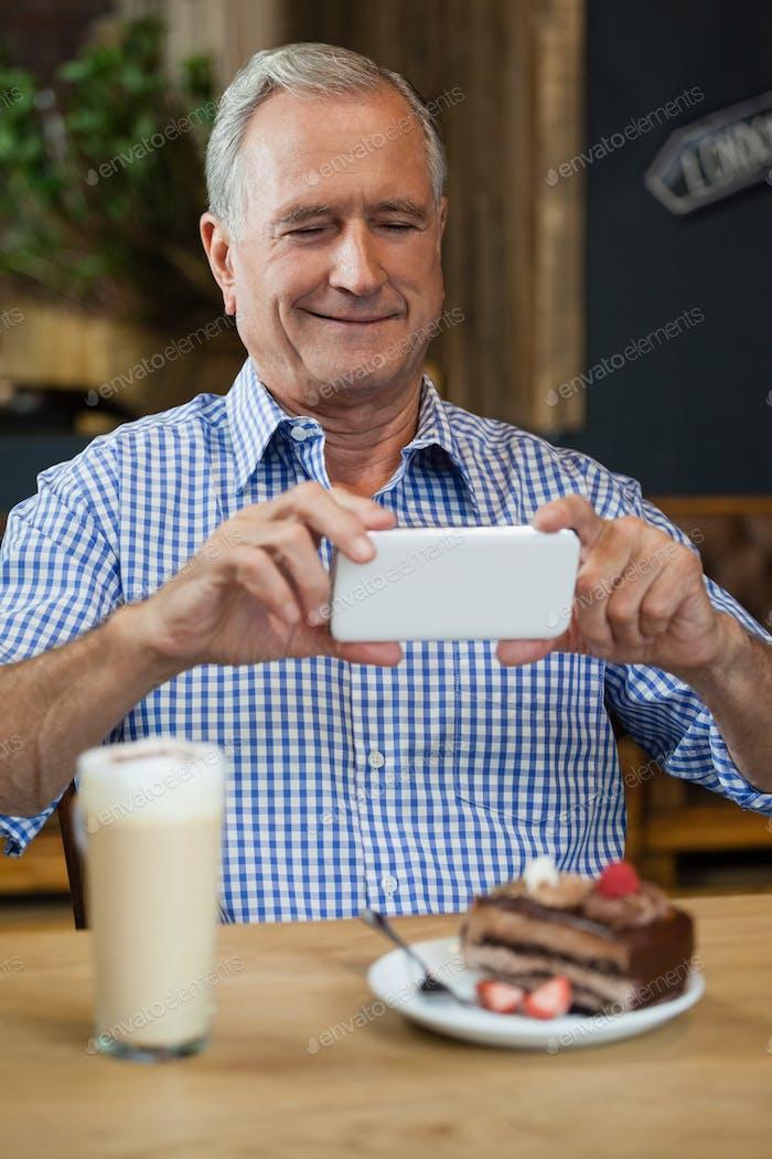 Senior Mann fotografiert Wüste in Platte am Tisch