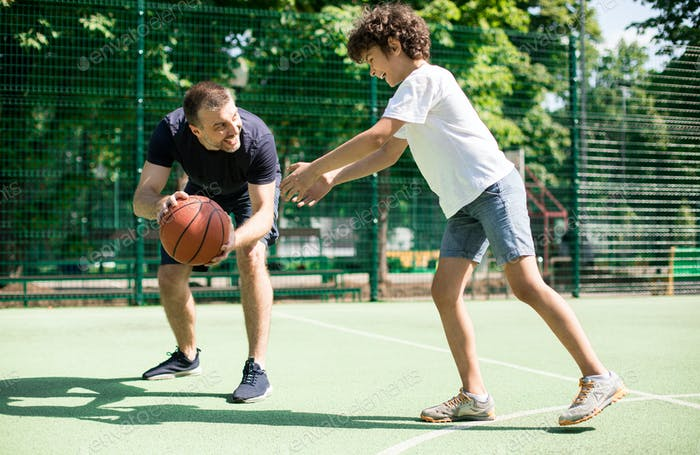 Cheerful man teaching boy how to play basketball
