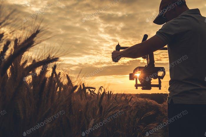 Operador de cámara de Vídeo con estabilización cardán tomando un disparo escénico de puesta de sol