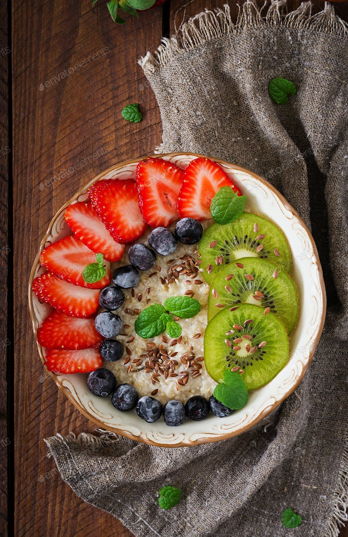 Tasty and healthy oatmeal porridge with fruit, berry and flax seeds