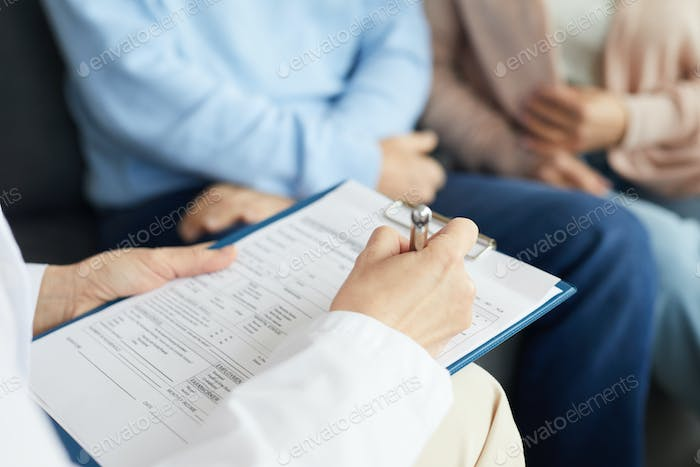 Doctor Filling in Patients Card Close Up