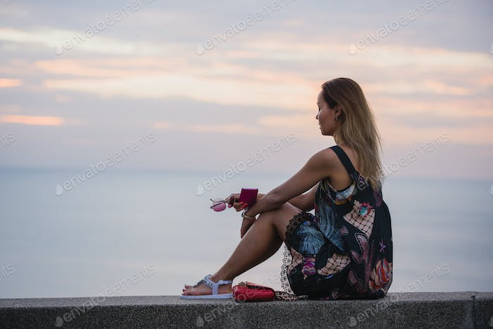 Beautiful woman sitting on embankment and enjoying the view, In a short dress, with mobile phone