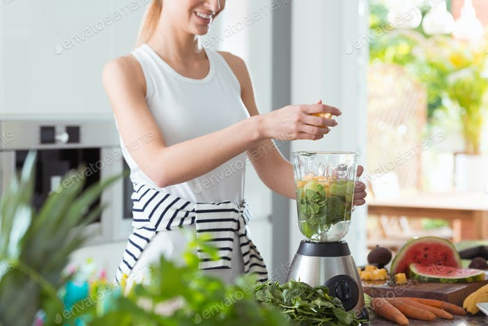 Happy vegan woman mixing vegetables