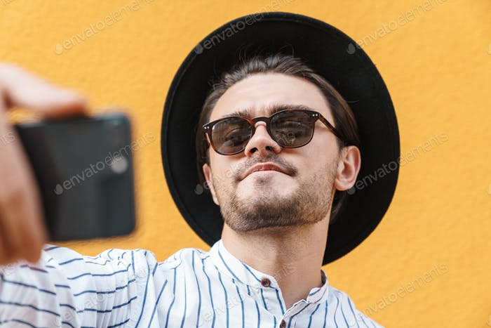Image of young masculine man wearing sunglasses and black hat smiling and taking selfie on cellphone