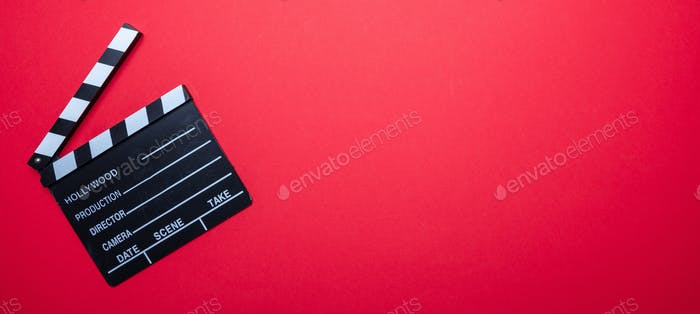 Movie clapperboard on red color background, banner, top view