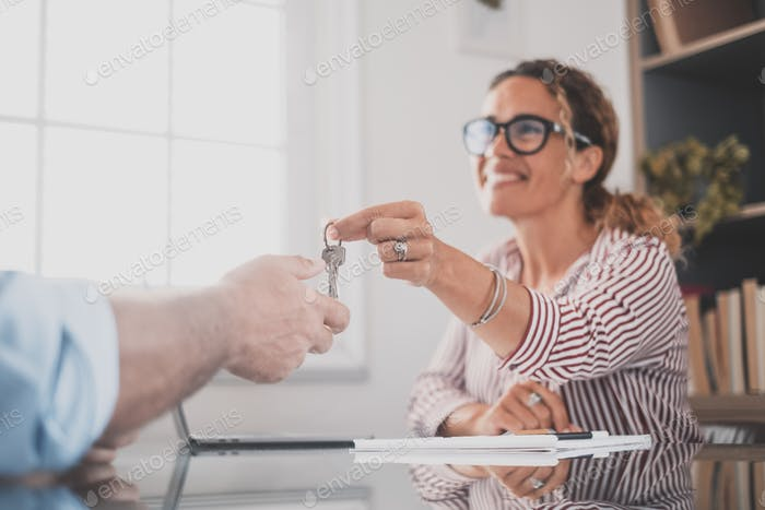 Crop close up of realtor give keys to man buyer or renter buying first home from agency.