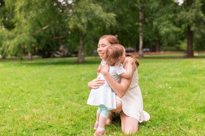 glückliche Mutter umarmt Baby Mädchen im Sommer park