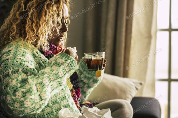 Coronavirus. Sick woman with cold flu influenza alone at home driniking herbal tea or medicine