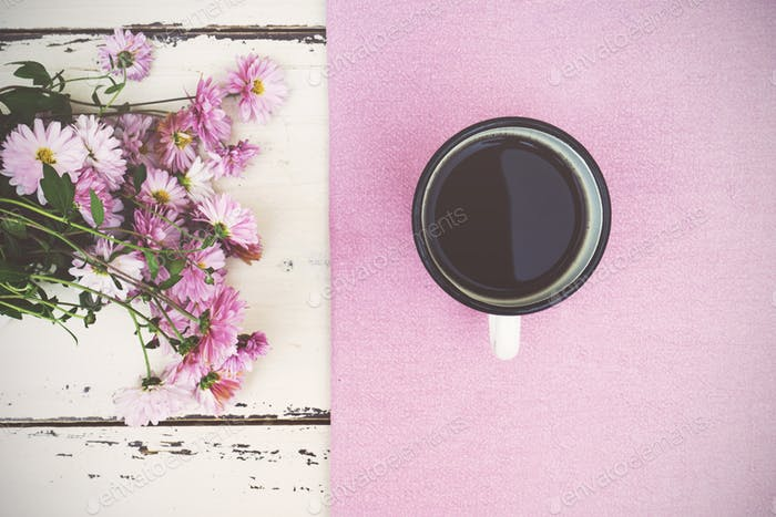 Cup of coffee and flowers at wooden background.